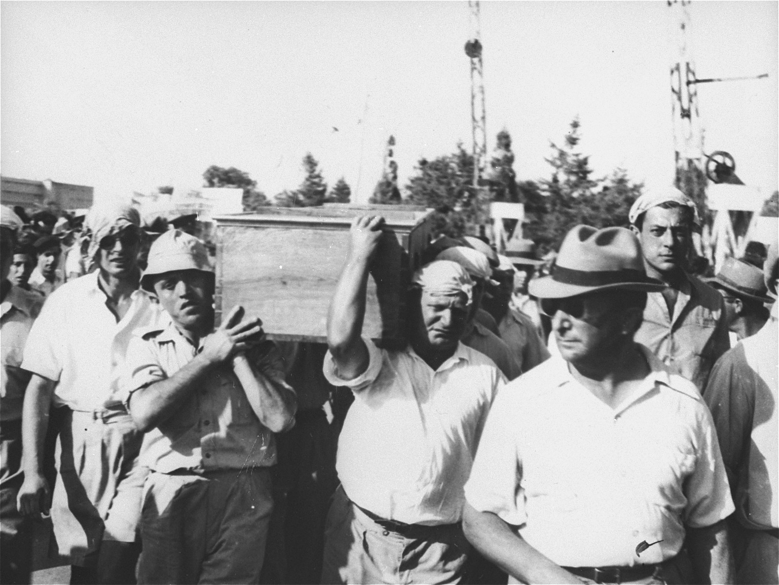 Crew members of the Exodus 1947 carry the coffin of fellow crewman, William Bernstein, who was killed in the struggle with the British off the coast of Haifa.  Pictured on the far left, carrying the coffin, is Jack V. Johnson, one of two non-Jewish crew members on board the Exodus.