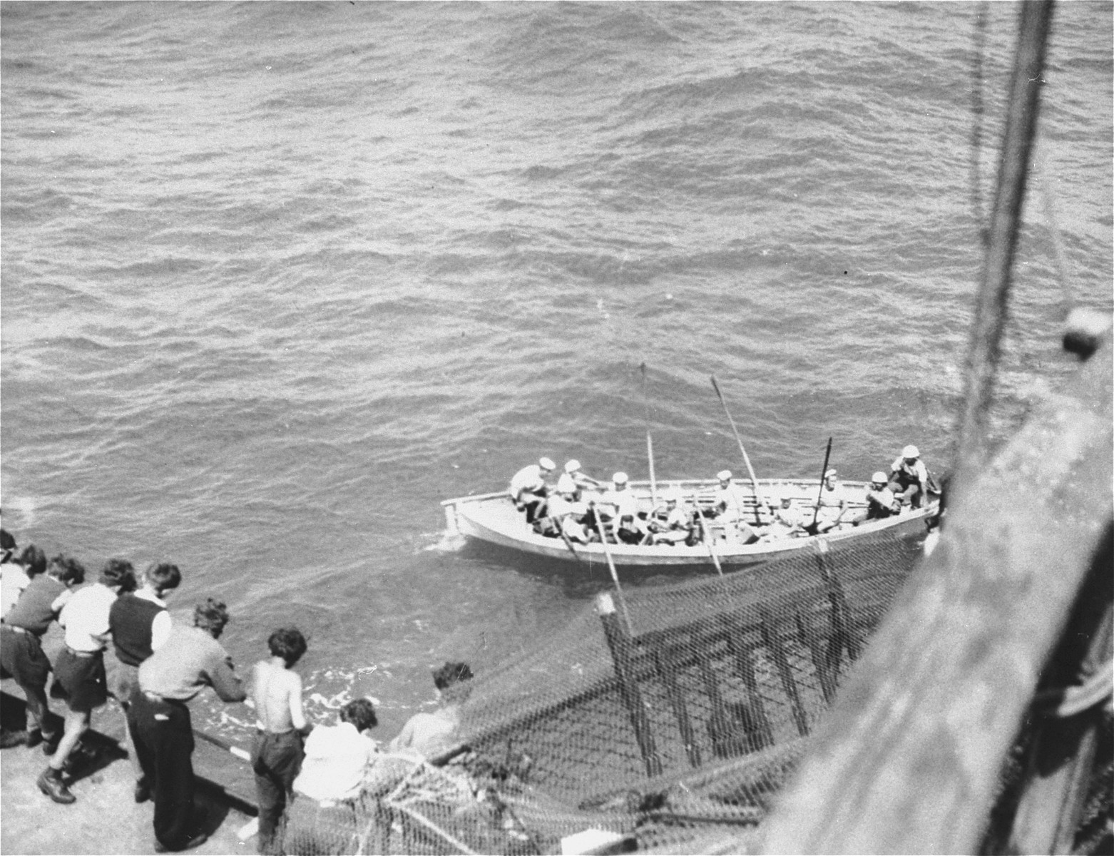 Passengers aboard the Exodus 1947 watch as the boarding party from the British destroyer, H.M.S. Ajax, approaches the illegal immigrant ship.