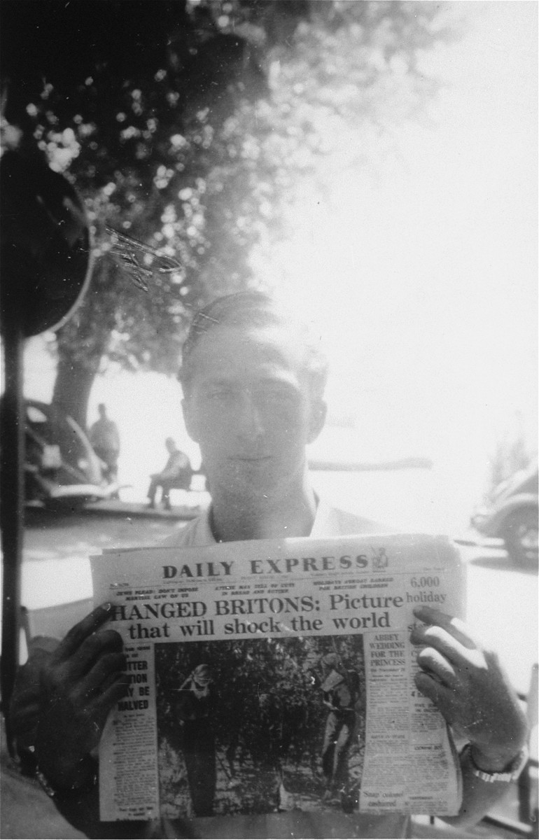 Former Exodus 1947 crew member Murray Aronoff, displays the headlines of a British newspaper reporting on the impact of the British interception of the illegal immigrant ship off the coast of Haifa.