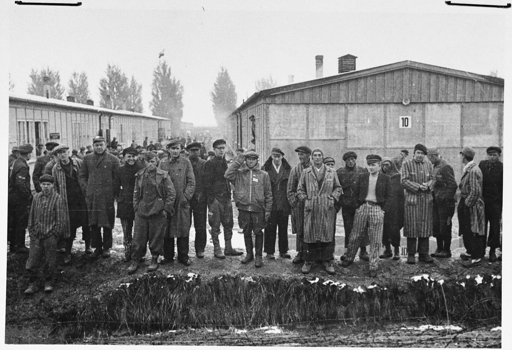 Group portrait of survivors standing next to the moat in the Dachau concentration camp following liberation.