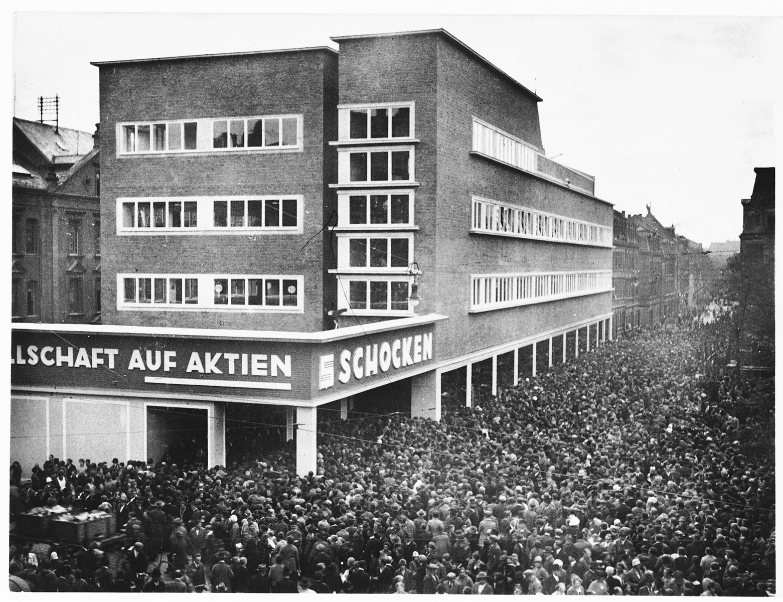 A huge crowd of people gather outside the Schocken department store in Nuremberg, Germany.