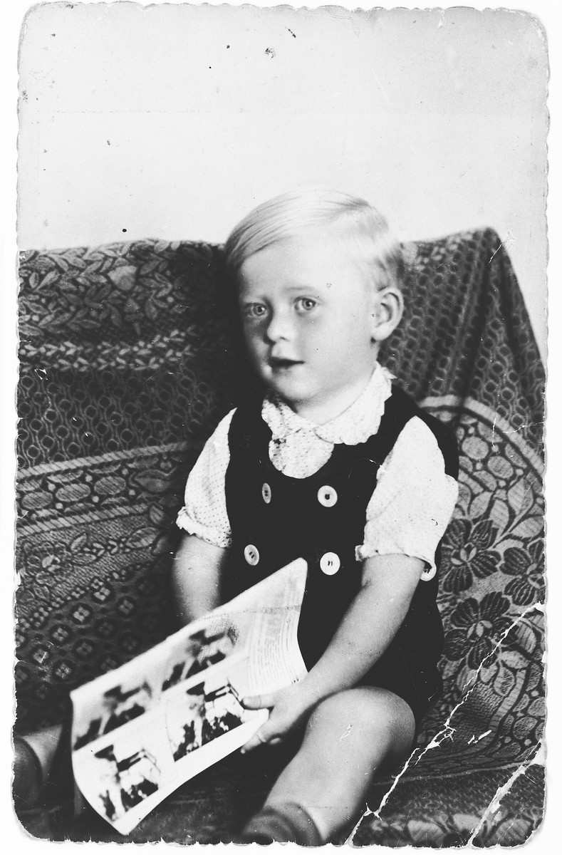 Close-up portrait of a little boy sitting on a couch with a magazine.   Pictured is Leszek, who perished in Auschwitz in 1943.
