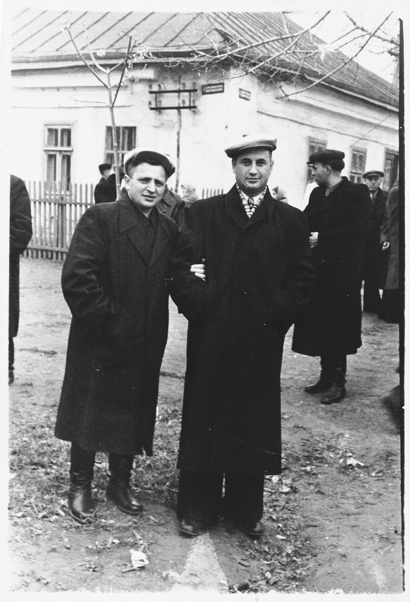 Shlomo Rachmil and a friend pose on a street corner in a small Russian town after liberation.