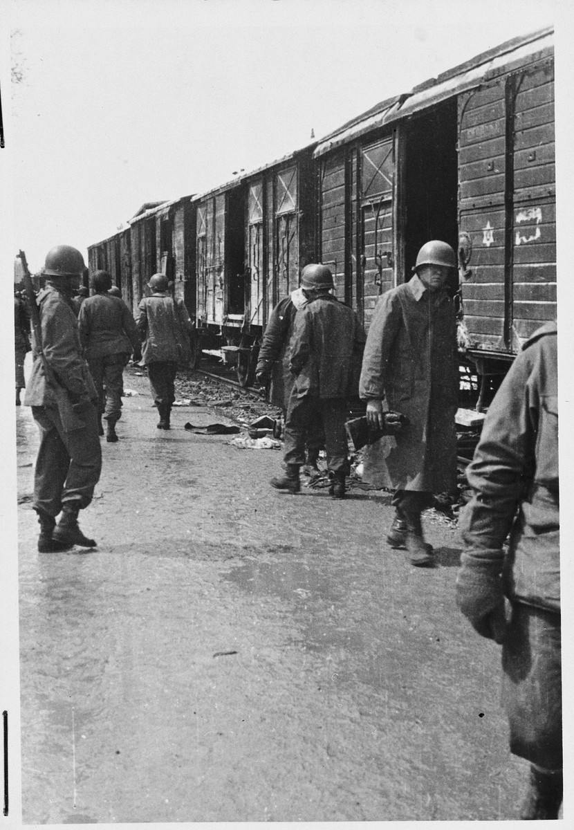 American soldiers walk by a train stationed in Dachau following liberation.