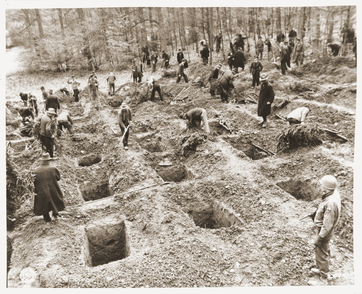 Under the supervision of an American soldier, German civilians from Suttrop dig graves for the bodies of 57 Russians, including women and one baby, exhumed from a mass grave outside the town.    The victims were forced to dig their own grave and then were shot by SS troops six weeks before the arrival of American troops.  On May 3, 1945, the 95th Infantry Division of the U.S. Ninth Army arrived in Suttrop and were informed by locals of the mass grave.  American troops forced the townspeople to exhume the grave after which Russian displaced persons in the area identified the bodies.  The victims were reburied in individual graves, and a U.S. Army chaplain conducted burial services.  Russians remaining in the area placed wreaths on the graves.