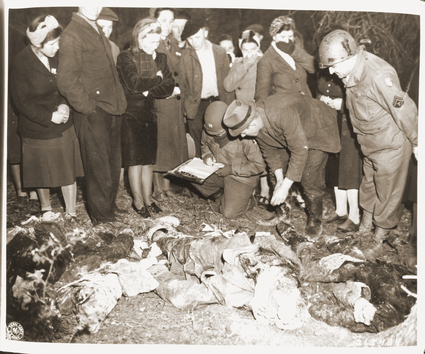 "A German civilian relays information found on the body of one of 57 Russians, exhumed from a mass grave outside the town of Suttrop, to a captain of the 95th Infantry division, U.S. Ninth Army.      The victims, including women and one baby, were forced to dig their own grave and then were shot by SS troops six weeks before the arrival of American troops.  On May 3, 1945, the 95th Infantry Division of the U.S. Ninth Army arrived in Suttrop and were informed by locals of the mass grave.  American troops forced the townspeople to exhume the grave after which Russian displaced persons in the area identified the bodies.  The victims were reburied in individual graves, and a U.S. Army chaplain conducted burial services.  Russians remaining in the area placed wreaths on the graves.  The original Signal Corps caption reads, ""GERMAN CIVILIANS FORCED TO EXHUME ATROCITY VICTIMS.  Amerian officers ordered German civilians of Suttrop, Germany, to exhume the bodies of 57 Russians killed by German SS troops and dumped into a mass grave before the arrival of troops of the Ninth U.S. Army.  Soldiers of the 95th Infantry Division were led by informers to the huge common grave of the victims, including women and one baby, May 3, 1945.  The Russians are said to have been forced to dig their own burial pit and then were shot so that their bodies would roll into it.  The executions are said to have taken place six weeks before U.S. troops entered  Suttrop.  The German civilians who were forced to exhume the bodies also were forced to search them for identification papers and then rebury them in individual graves.  A U.S. Army chaplain performed burial rites and wreaths were placed on the greaves by Russians remaining in the area.  Before burial, all German civilians in the vicinity were ordered to view the atrocity victims.  BIPPA                                                                     EA 65391  THIS PHOTO SHOWS:  A german civilian gives the information he has just obtained from a corpse to a captain of the 95th Infantry Division, Ninth U.S. Army.  U.S. Signal Corps Photo ETO-HQ-45030.  SERVICED BY LONDON OWI TO LIST B CERTIFIED AS PASSED BY SHAEF CENSOR"""