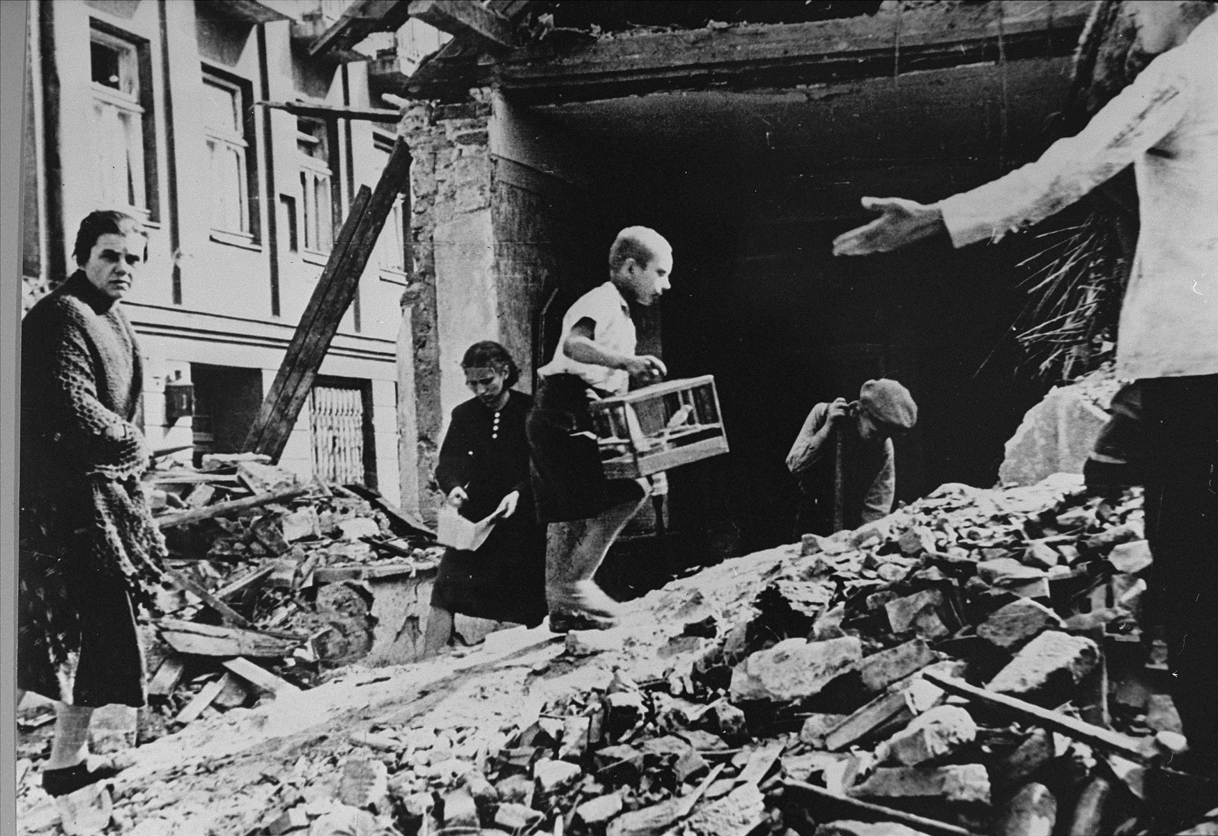 "Polish civilians salvage items from the ruins of their homes in Warsaw after a German air raid.   The child carrying the birdcage is Zygmunt Askienow.  In the words of photographer Julien Bryan, ""Not far from the center of town a bomb had hit an apartment house and exposed the first, second, and third floors.  A boy was walking dazedly back and forth carrying the one possession he had found -- a canary in its cage.  He walked up and down over a pile of stones and bricks.  Under the pile there were nine or ten bodies, so the neighbors told us, not yet recovered."" [Source: Bryan, Julien.  ""Warsaw 1939 Siege, 1959 Warsaw Revisited.""  Warsaw, Polonia, 1959, p. 24]"