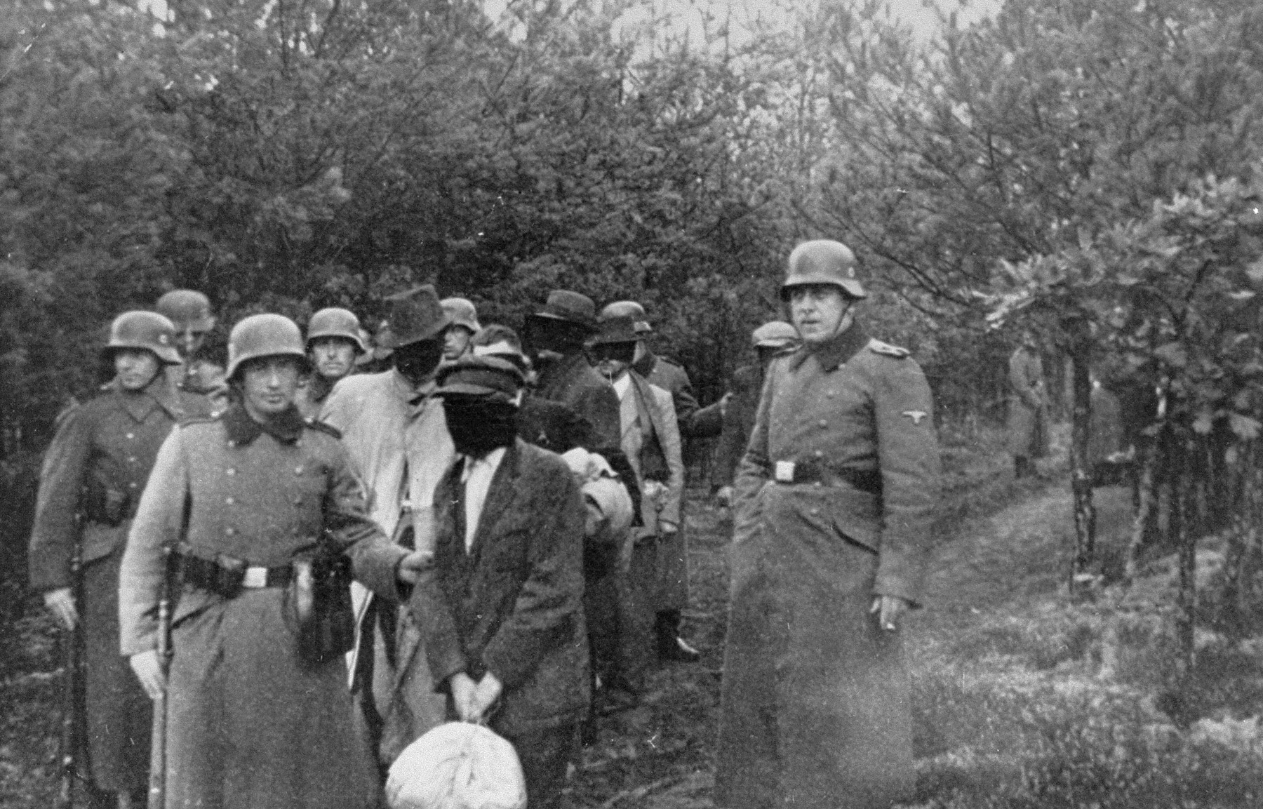 SS personnel lead a group of blindfolded Polish prisoners to an execution site in the Palmiry forest near Warsaw.  These civilians had been held in the Palmiry and Mokotow prisons in Warsaw.