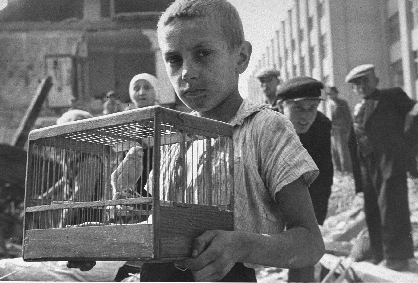 A young boy, Zygmunt Askienow, holds the cage containing his pet canary that he rescued from the ruins of his family's home in Warsaw.    Zygmunt survived the war.