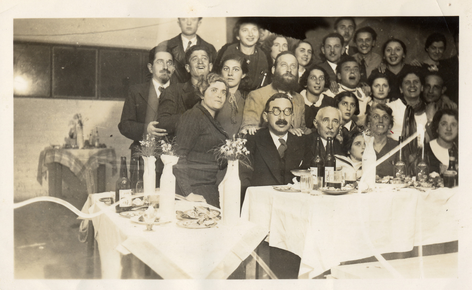 Group portrait of the employees of the Bialer textile factory attending a Passover seder together.  Aharon Bialer is standing on the far left (third row).  Rachel Bialer is seated second from the right.  Standing in the second row are Tonia Bialer (third from left) and Noemi Bialer (fourth from right).