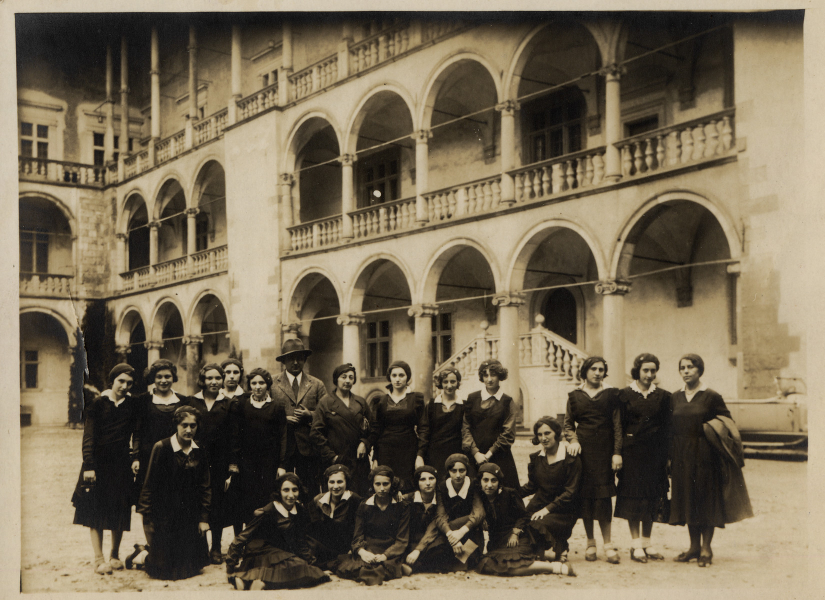 Group portrait of girls from the Hochsztajnowa Gymnasium of Lodz in the courtyard of the Wawel Castle in Krakow where they went on a field trip.  Tonia Bialar is seated in the front row on the far left.