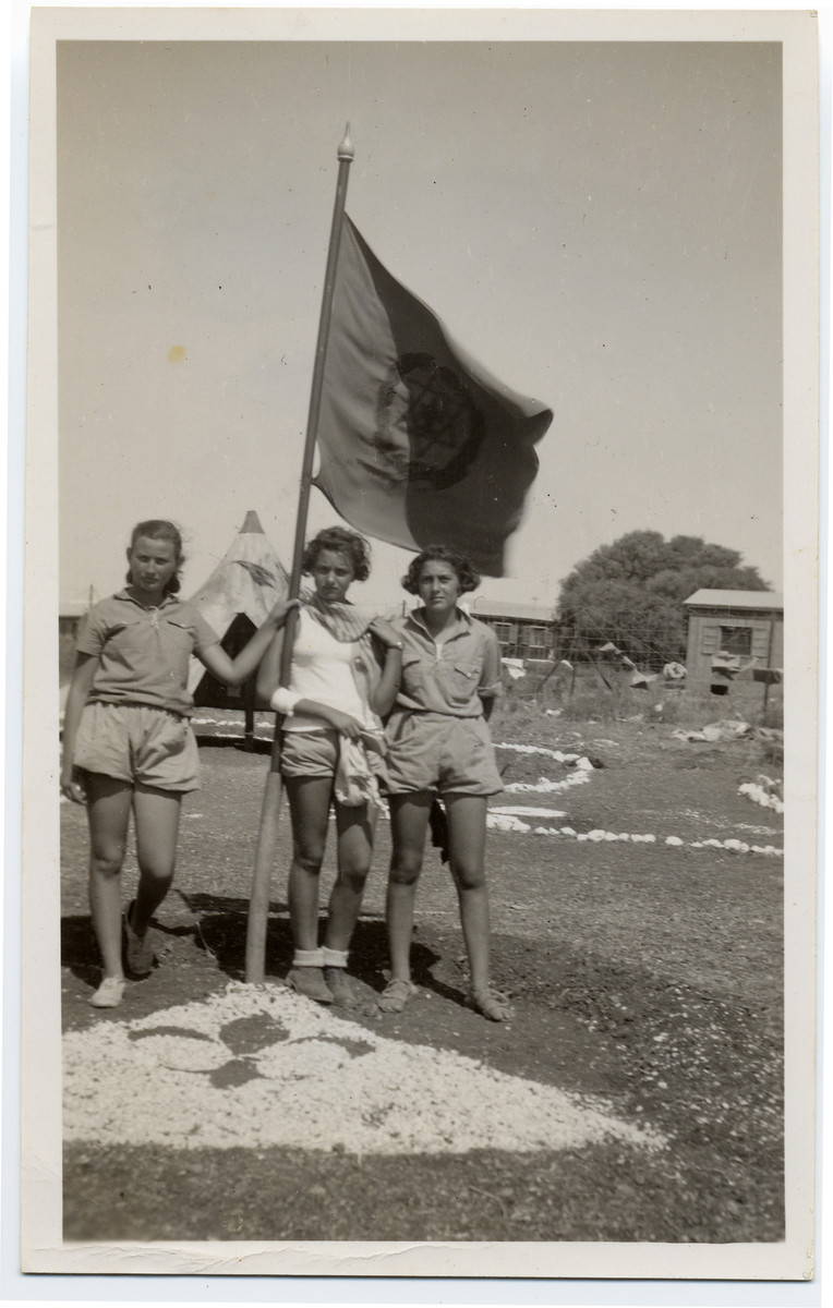 Noemi Bialer (right) poses with two friends beneath a Shomer Hatzair youth movement flag in a summer camp in Palestine.