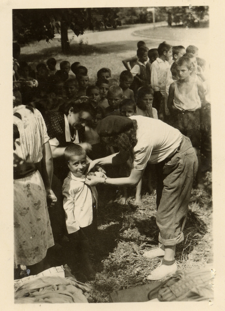 Tonia Lechtman dsitributes clothing and shoes to Jewish orphans on behalf of UNRRA at an unidentified children's home after the war.