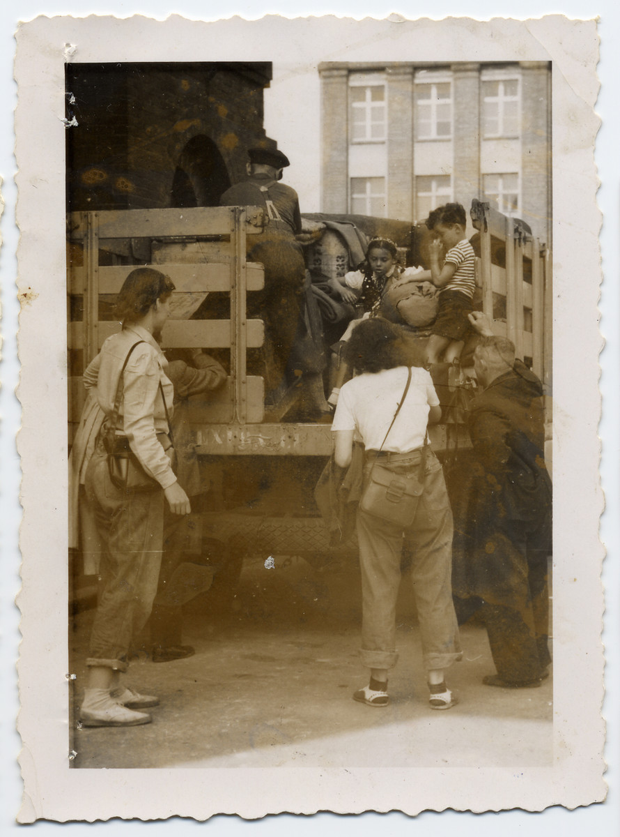 Tonia Lechtman helps board Jewish orphans onto the back of a truck to return them to Poland while working as a social worker after the war.