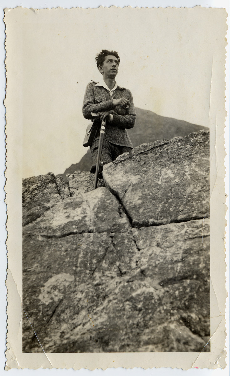Avraham (Romek) Bialer poses on a cliff while hiking in Palestine.