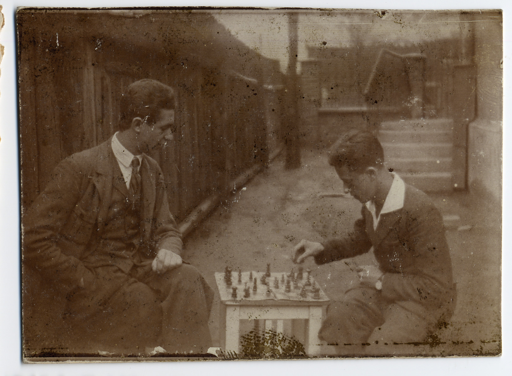 Julek (Joel) Bialer (right) plays chess outside in a courtyard with his father, Aron.