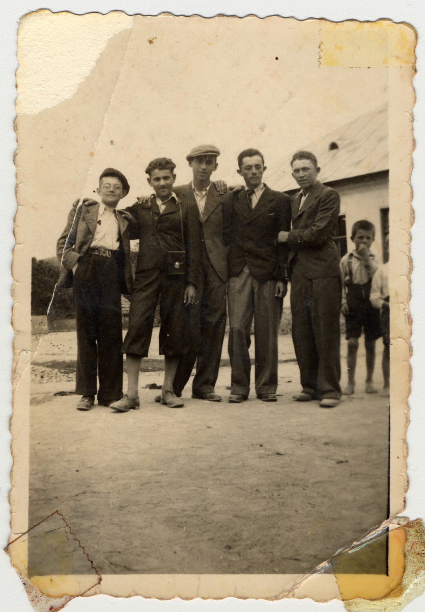 Group portrait of Jewish teenagers standing outside a home in Mukachevo.  Among those pictured are Menachem Monush Kallus (right), brother of the donor and his cousin Chaim Neugreshel (center).