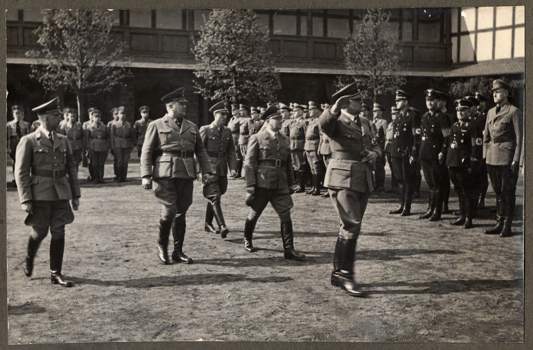 Nazi officials salute and walk in a courtyard at a seminar for Reich training and schooling in Erwitte.  Pictured from left to right are: Alfred Meyer,  Gauleiter Westfalen-Nord; Heinrich Vetter, Stellvertretenden Gauleiter von Westfalen-Sued; Friedrich Schmidt;  and Hans Frank (saluting).