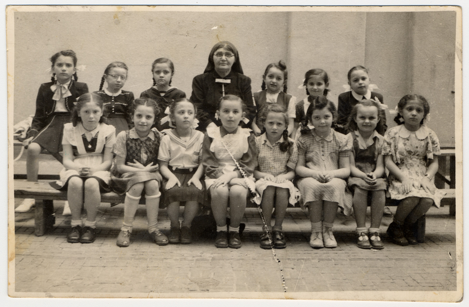 Group portrait of girls in an Orthodox Jewish elementary school in Budapest.  Among those pictured is Zsuzsa Rubin in the back row to the right of the teacher.