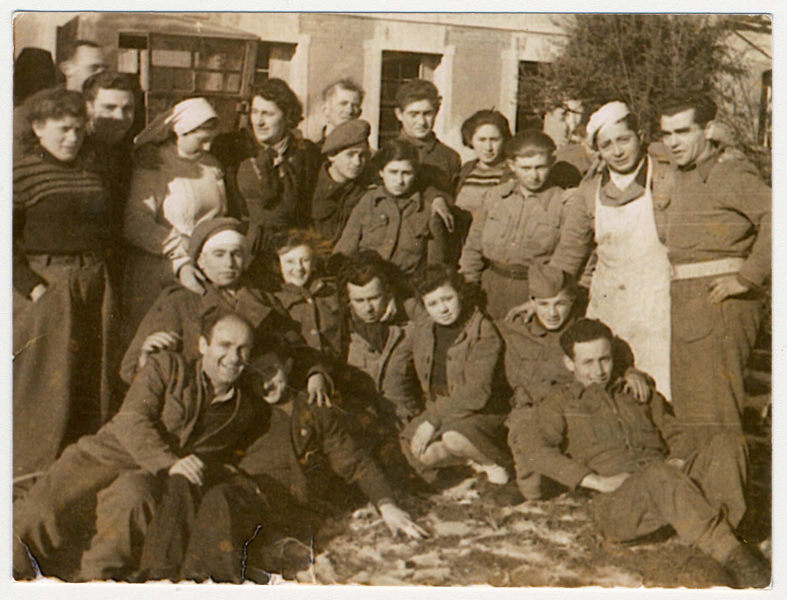Jewish youth pose for a group portrait in a kibbutz hachshara in Italy.  Among those pictured is Josef Fischer, wearing a cook's apron (standing second from the right).  Standing to his right is Sgt. Noach Kleiner from the Jewish Brigade.  Mordechai, the group leader is in the front left.  Standing in the center is Rivke Domawaska.