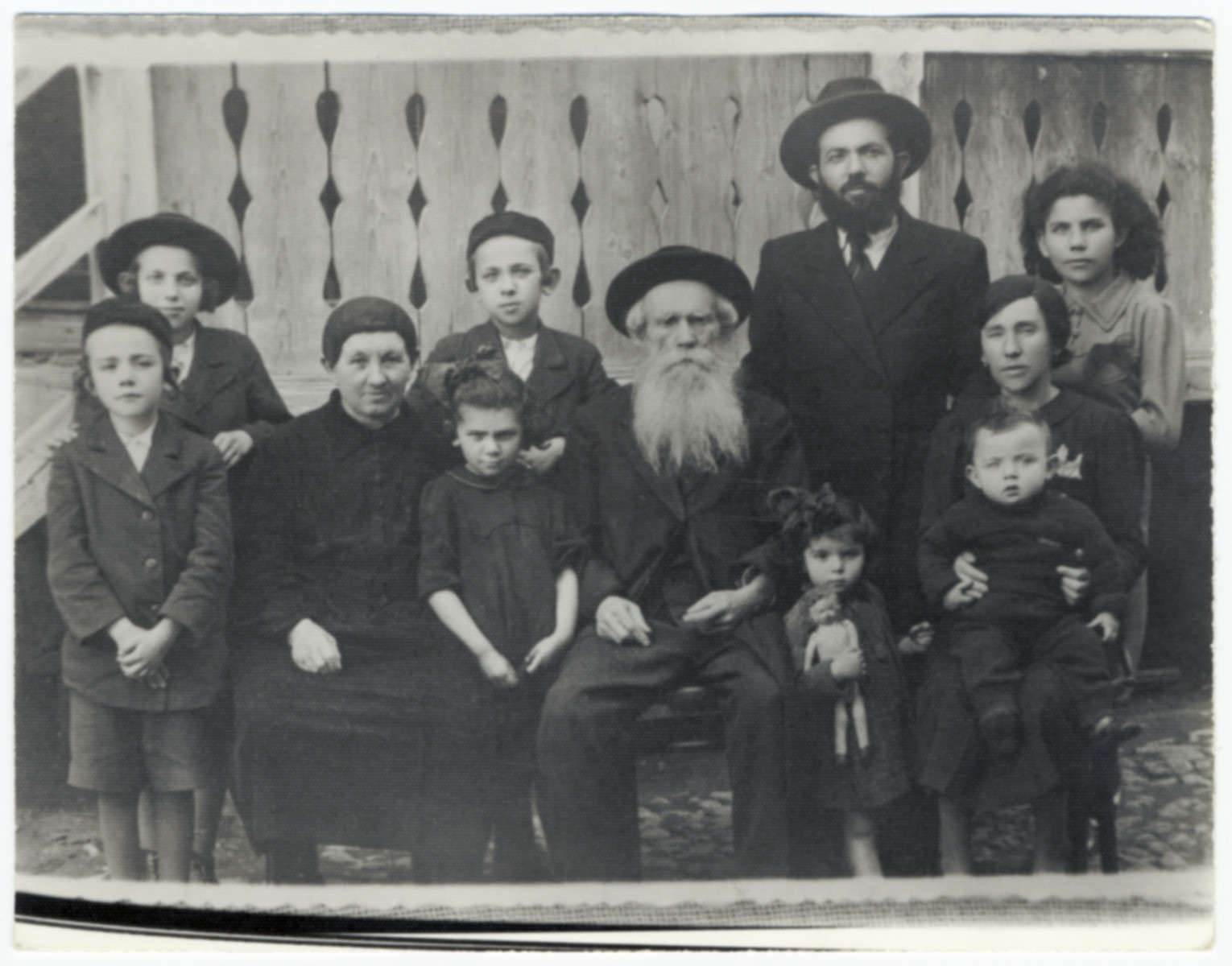 Group portrait of the family of Rabbi Fishel Ostreicher.  He is pictured with his parents and children.  Rabbi Ostreicher served as secretary of the Jewish community in Munkacs.