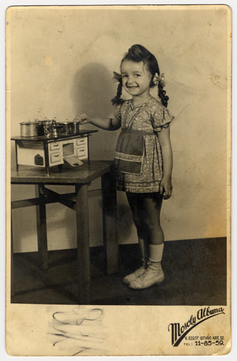 Sutdio portrait of a Hungarian Jewish girl standing next to a toy kitchen and pretending to cook.  Pictured is Zsuzsa Rubin.  This photograph was sent to her uncle Izso Stern in a Hungarian labor battalion.  One month after this photograph was taken, Germany seized control of Hungary and began implementing the Final Solution there.