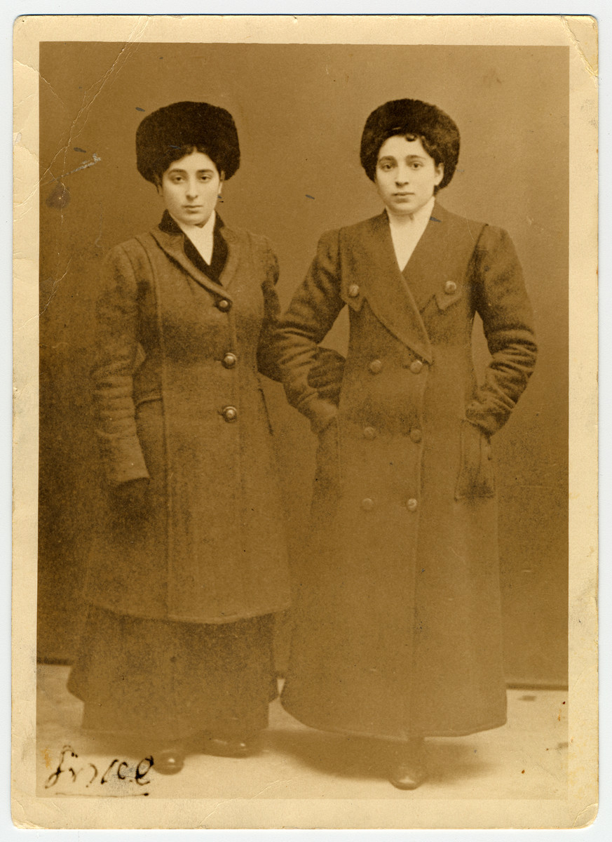 Studio portrait of two Jewish women wearing winter coats and hats in Finland.  Pictured on the left is Sara Domawaska.  To her right is her sister Asya Riemer.  They had been sent to Finland to work as housekeepers.