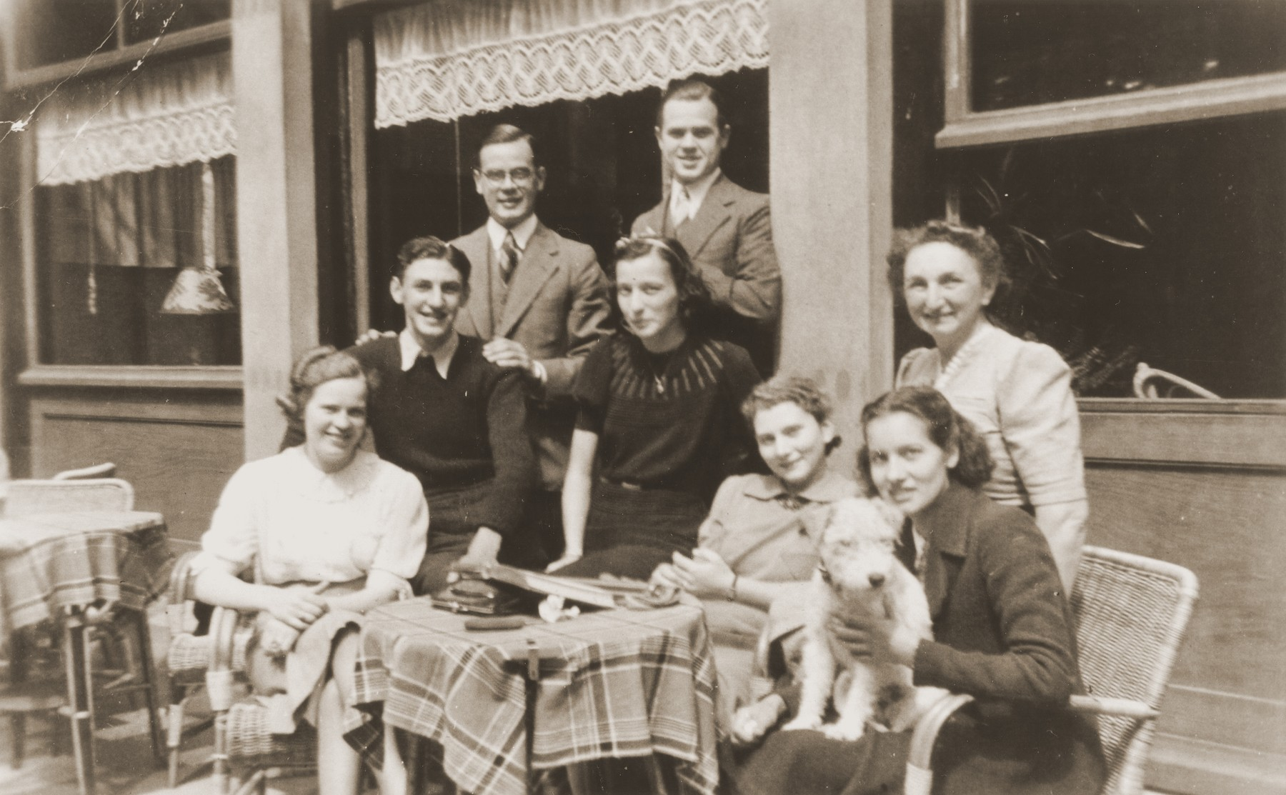 The Jacobsthal family poses at an outdoor cafe in Amsterdam.  Hilde Jacobsthal is pictured at the lower right.