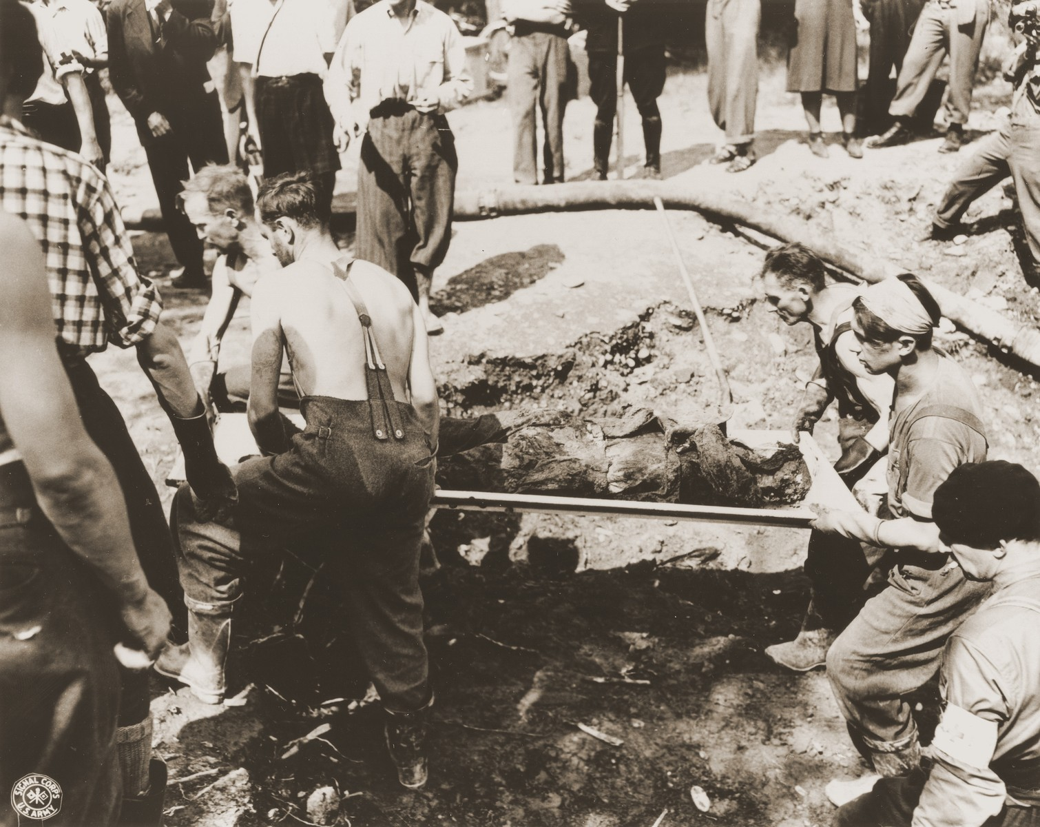 French civilians remove a charred corpse from the ruins of the church in Oradour.