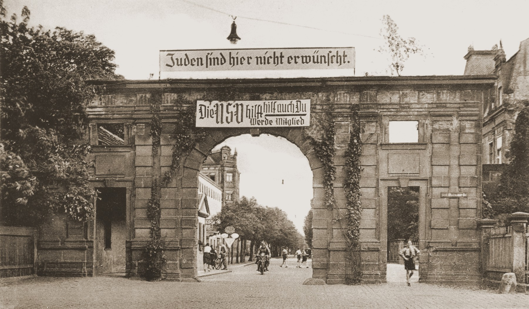 View of Nuernberger Tor, one of the entrances to the University of Erlangen, on top of which a banner has been placed stating that Jews are not desired here.  Below it hangs a Nazi party recruitment banner.