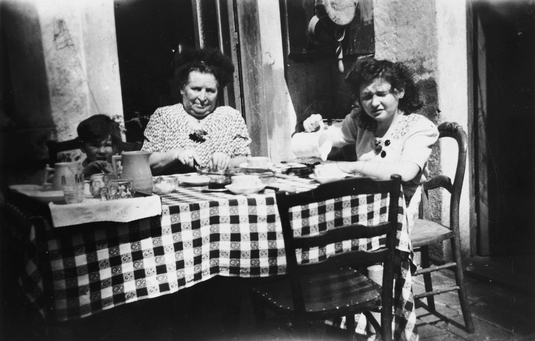 Hena Kohn and her younger cousin Marcel Shumiliver sit down to eat with their Belgian rescuer Alix Robert while in hiding.