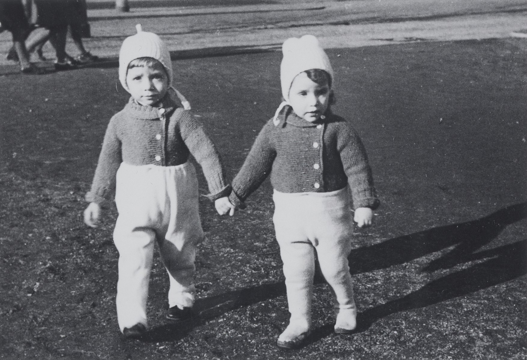 Two Jewish twins walk outside holding hands while on an outing at the lake with their parents.  Pictured are Rene and Renate Guttmann.