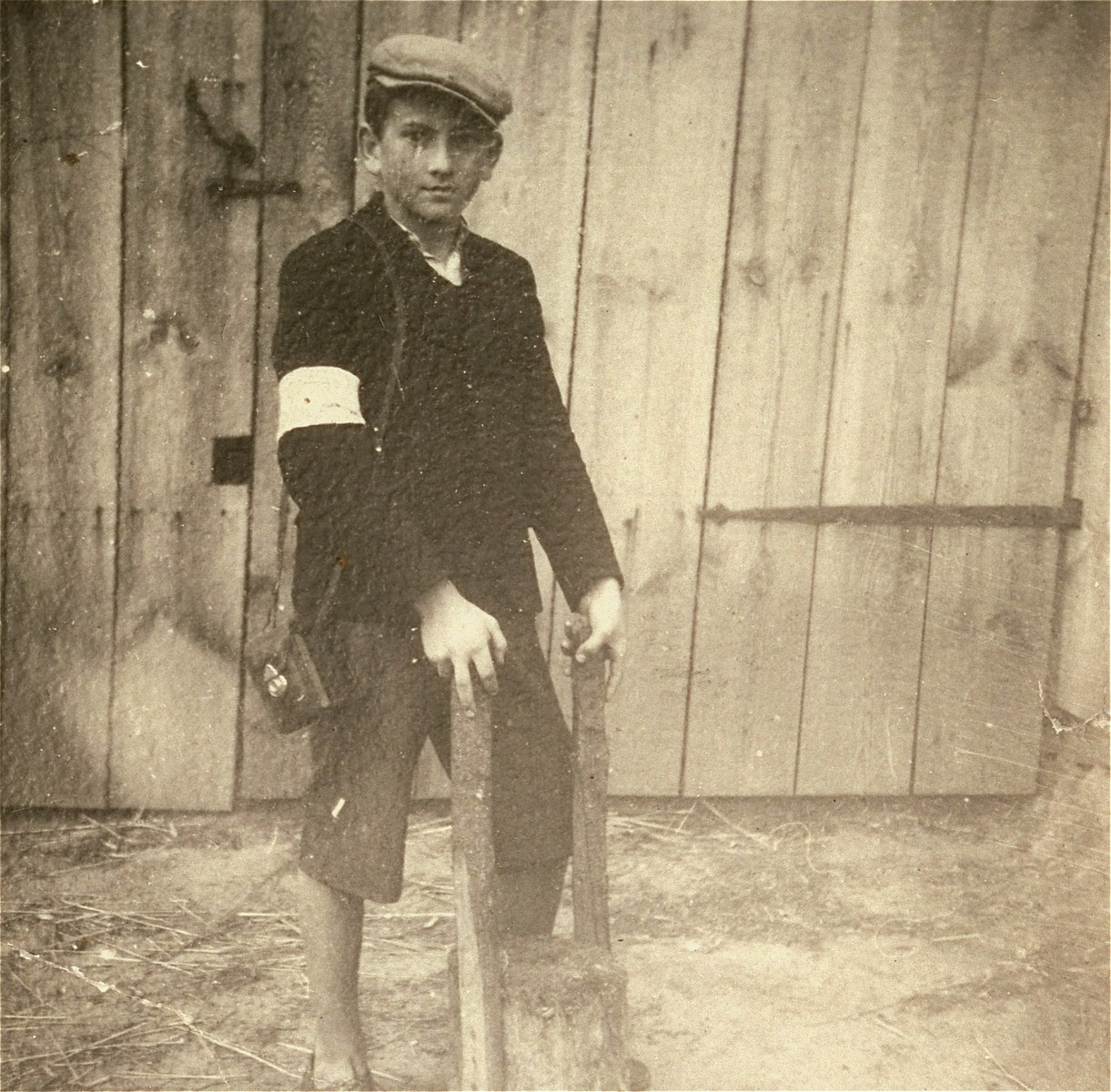 A Jewish youth wearing an armband poses holding a farm implement in the Kolbuszowa ghetto.  Pictured is Manius Notowicz.