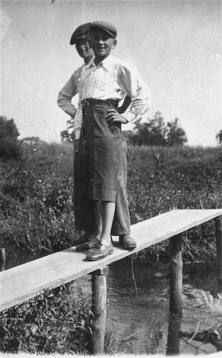 Two Jewish youth pose on a wooden beam in the Kolbuszowa ghetto.  Pictured is Manius Notowicz and a friend.
