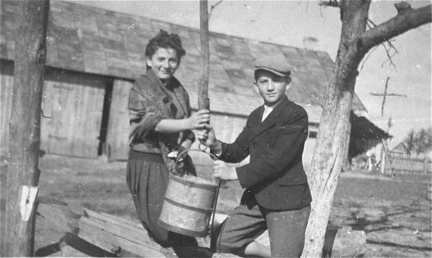 Two Jewish siblings draw water from a well in the Kolbuszowa ghetto.  Pictured are Manius and Niunia Notowicz.