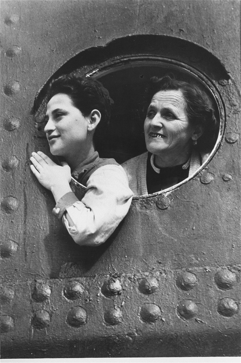 Jewish refugees look out through the portholes as they arrive in Haifa harbor.  The photograph came from a photo album presented to President Eisenhower by Israeli Prime Minister David Ben Gurion.