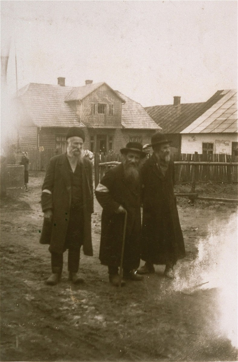 Three elderly Jews walk along an unpaved street in the Kolbuszowa ghetto.    Pictured from left to right are: Izyk Ortzman, Mosze Kurtz, and Avrum Weissman.