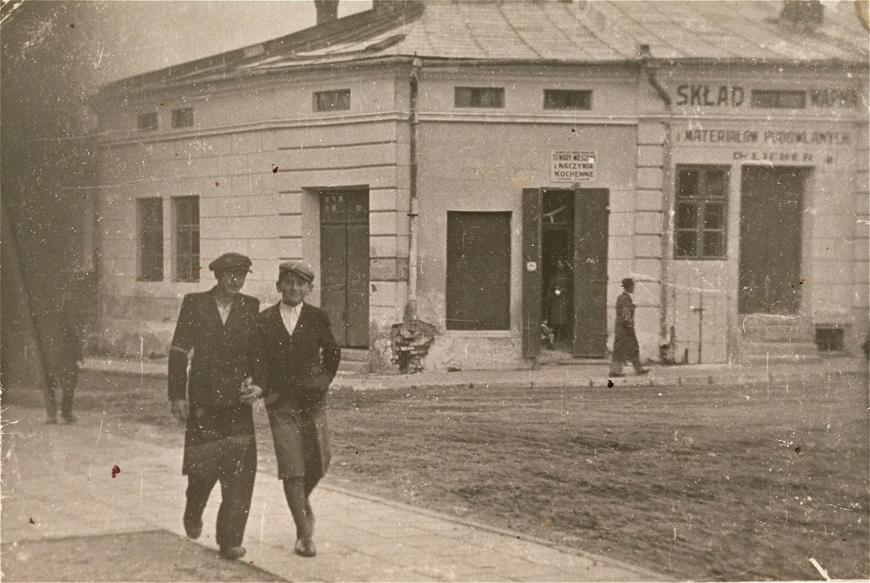 Two friends walk along a street in the Kolbuszowa ghetto.  Pictured is Manius Notowicz (right) with a friend named Grinstein in front of Lieber's building supply store.
