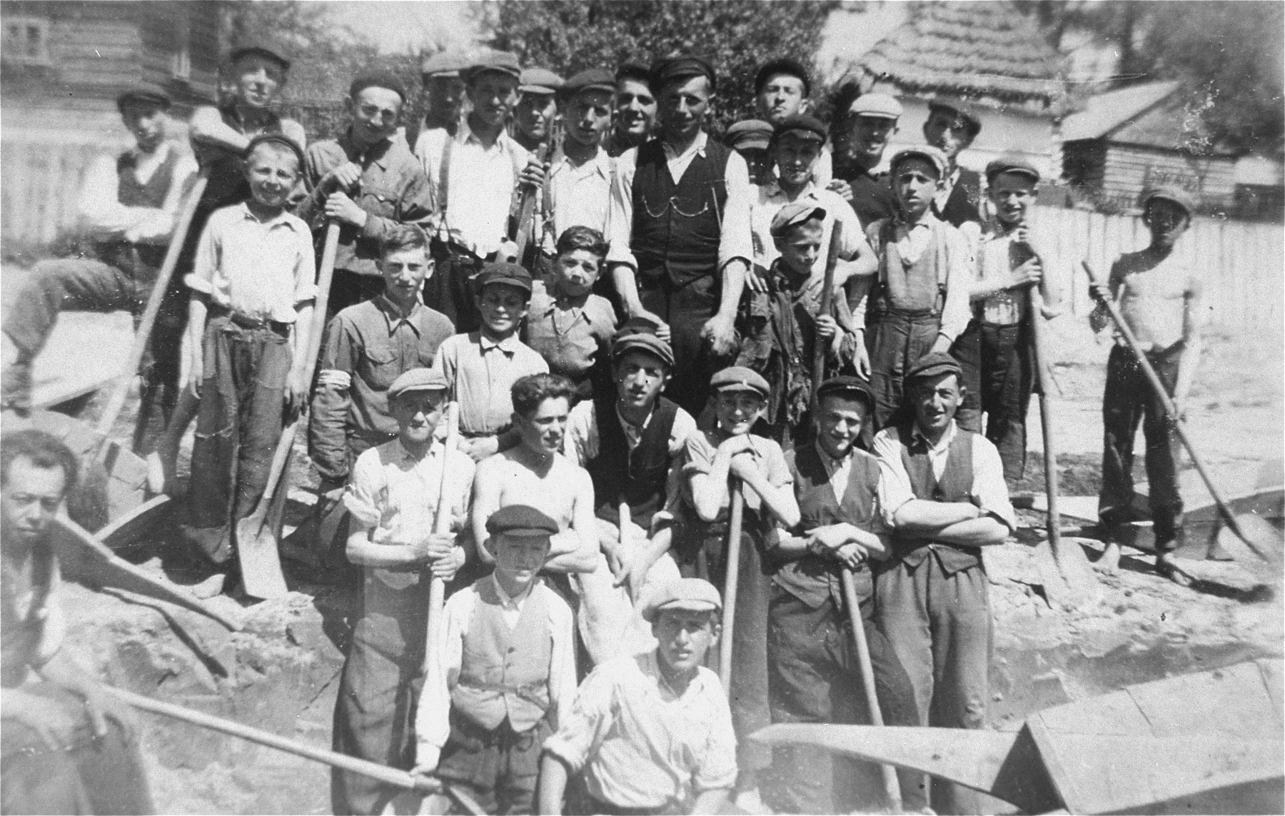 Group portrait of Jewish forced laborers holding shovels in Kolbuszowa.