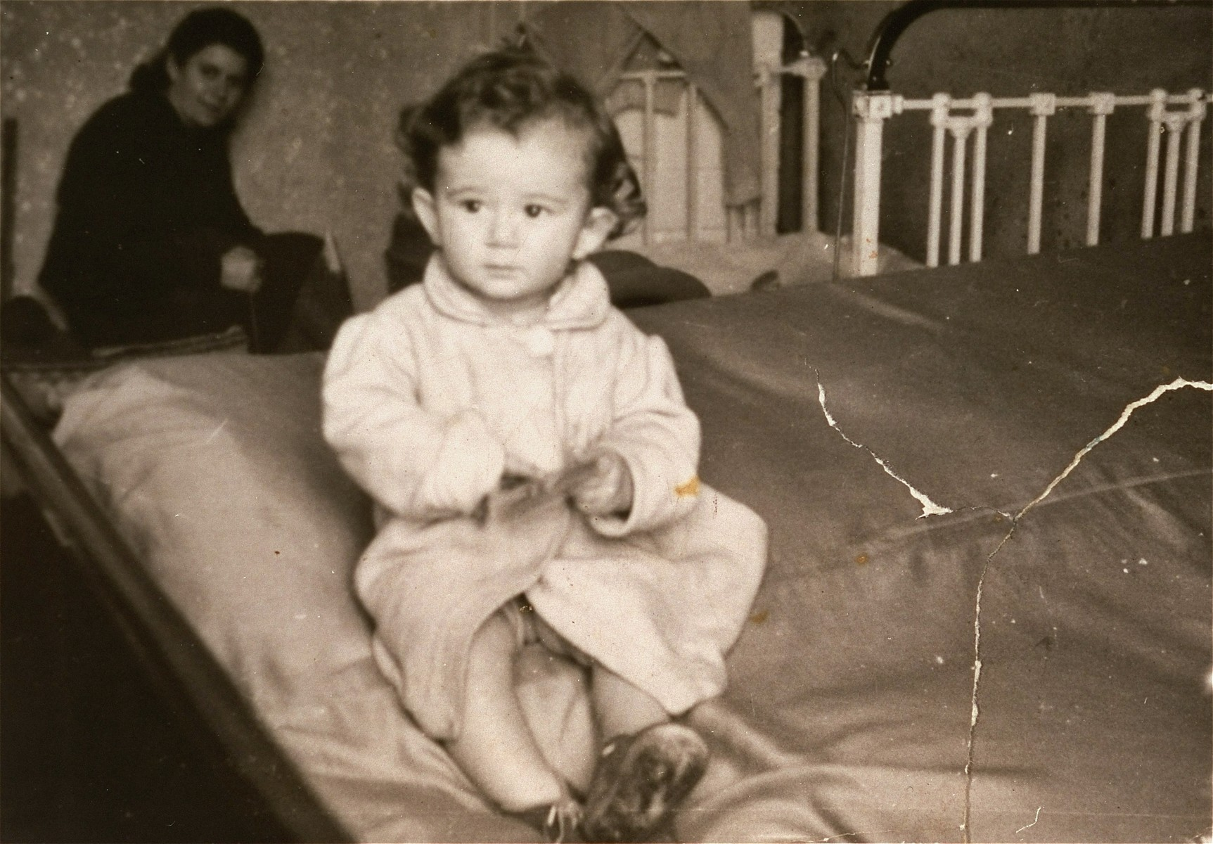 One-year-old Jurek Kaiser sits on a bed in his parents' apartment in the Kielce ghetto.