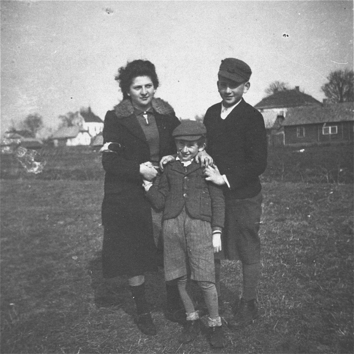 Three Jewish siblings pose outside in the Kolbuszowa ghetto.  Pictured are Manius, Leon and Niunia Notowicz.