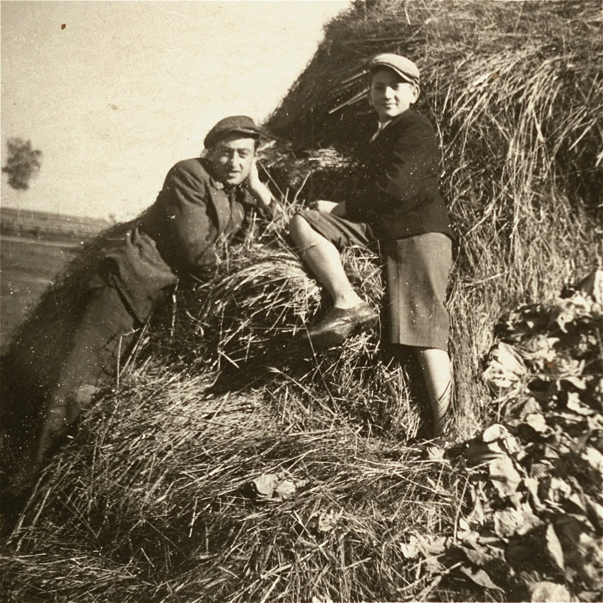 Two Jewish youth sit on a haystack in the Kolbuszowa ghetto.  Pictured are Manius Notowicz and his friend Mondi Stub.