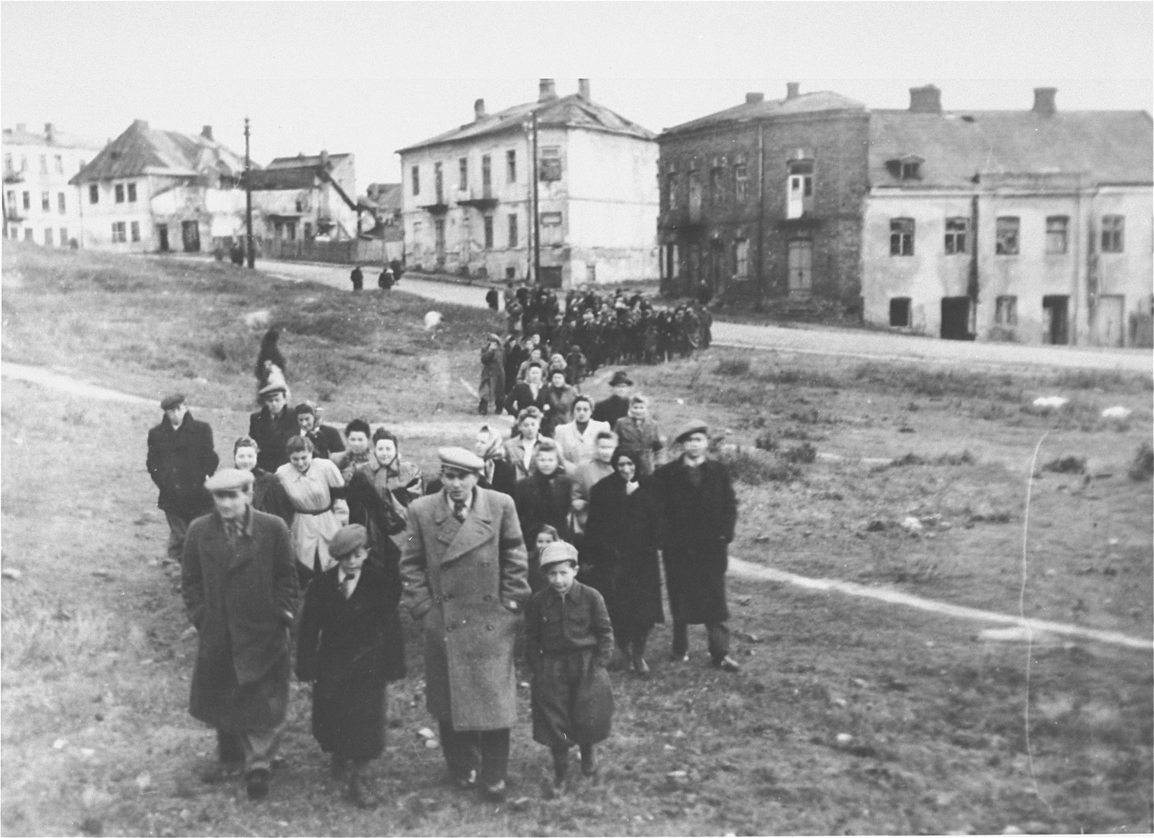 Survivors from Ostrowiec walk toward the site of a mass grave for 2000 Jews shot during the October 1942 action.