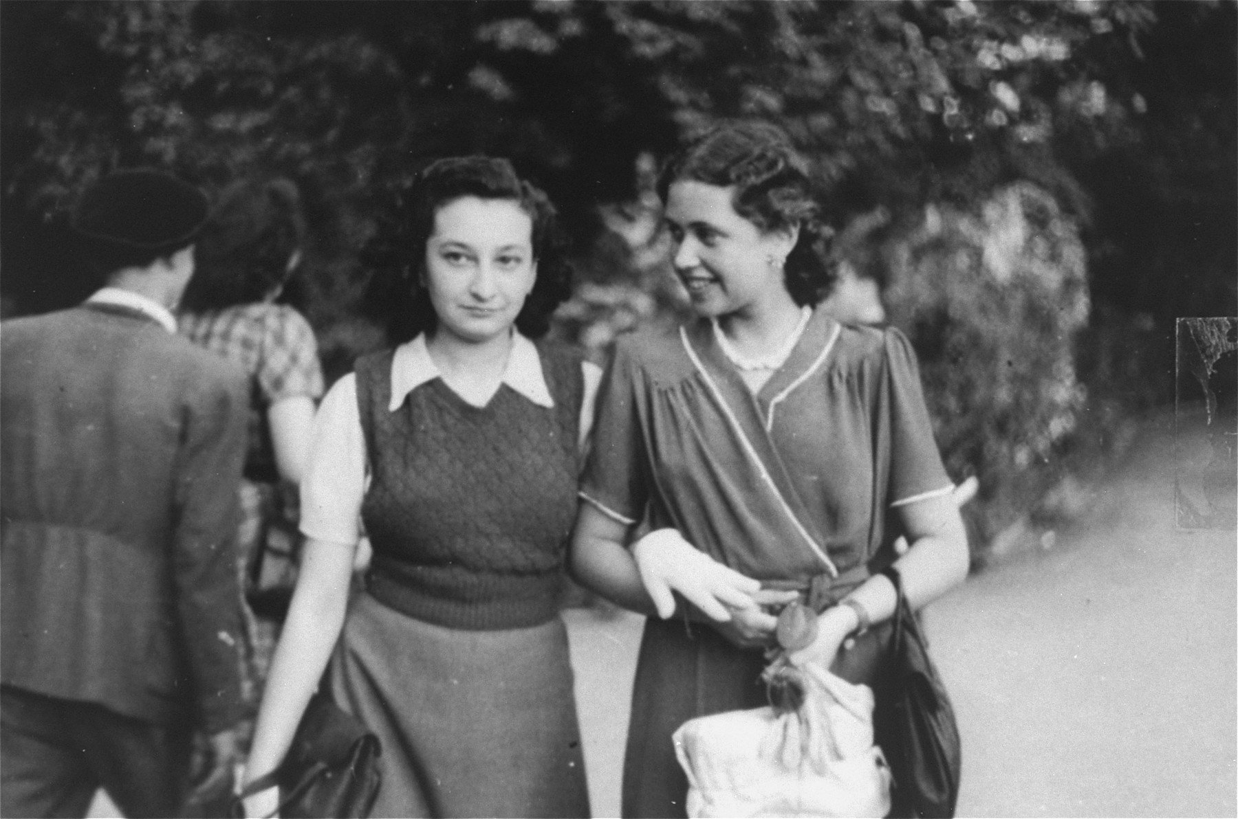 Two Jewish female friends walk in a park in Bucharest just after the liberation.  Pictured are Jeanine Gutman (left) with her friend Valerie Zigmund.