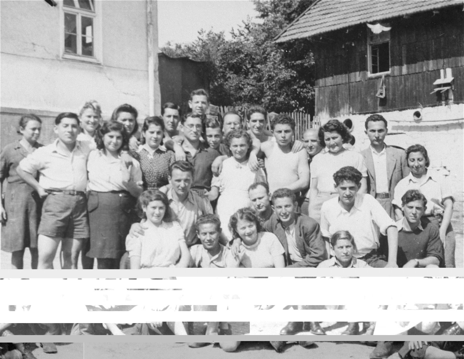Group portrait of members of the Kibbutz Buchenwald hachshara (Zionist collective) in Geringshof, Germany.  Among those pictured are Motek Nussenbaum, Roman Mor, Karla, Freddie Diamant, Yisrael Luzer, Blumah, Shmuel Mor, Shlomo Shiff, Izik Neuman, Aliza, Sylvia and Levin.
