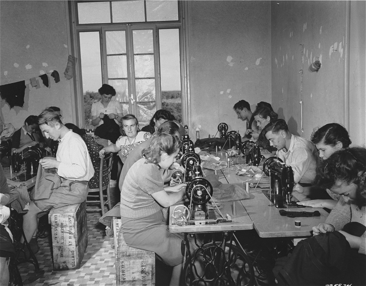 Young men and women work in a  sewing workshop at a Jewish DP camp in Italy.    Vocational training was provided by the American Joint Distribution Committee, while the machines and material were provided by UNRRA.