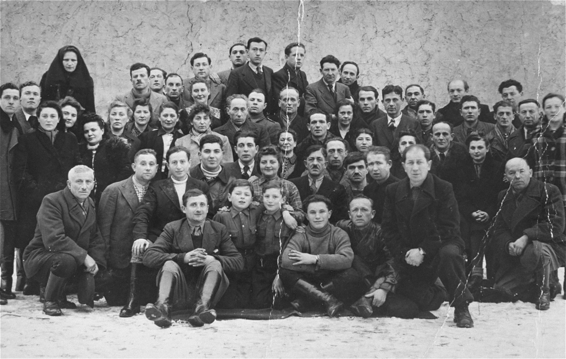 Group portrait of Polish Jewish survivors in Kielce.  Many of them were killed one year later in the pogrom in 1946.  Samuel Rutkowski and his father Moshe Rutkowski have been tentatively identified (first row, second from the right, wearing a turtleneck; and second row, third from the right with a mustache.)