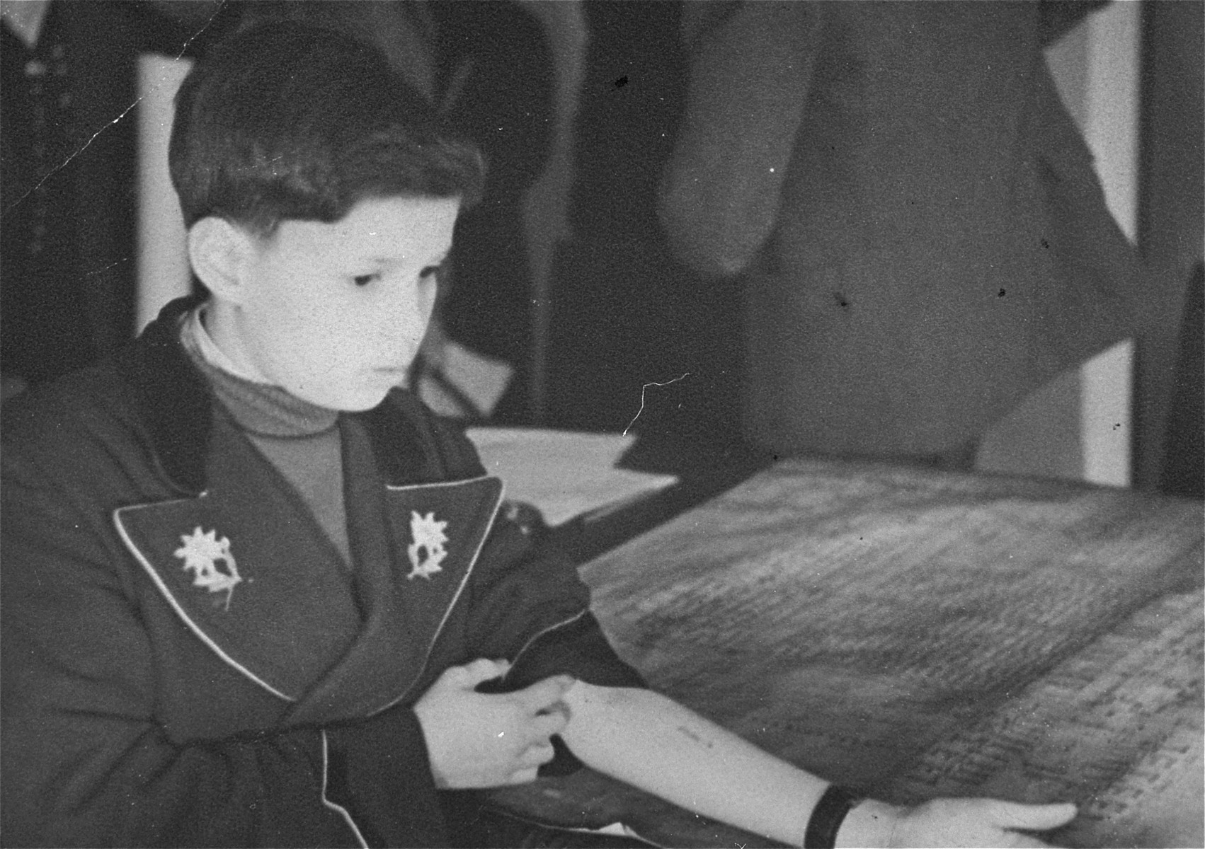 Child survivor, Luigi Ferri, shows the Auschwitz prisoner number tattooed on his arm, B7525.    The photograph is inscribed to the donor, Frieda Fisz Greenspan, a Polish Jewish survivor who befriended Luigi after the war in Krakow.