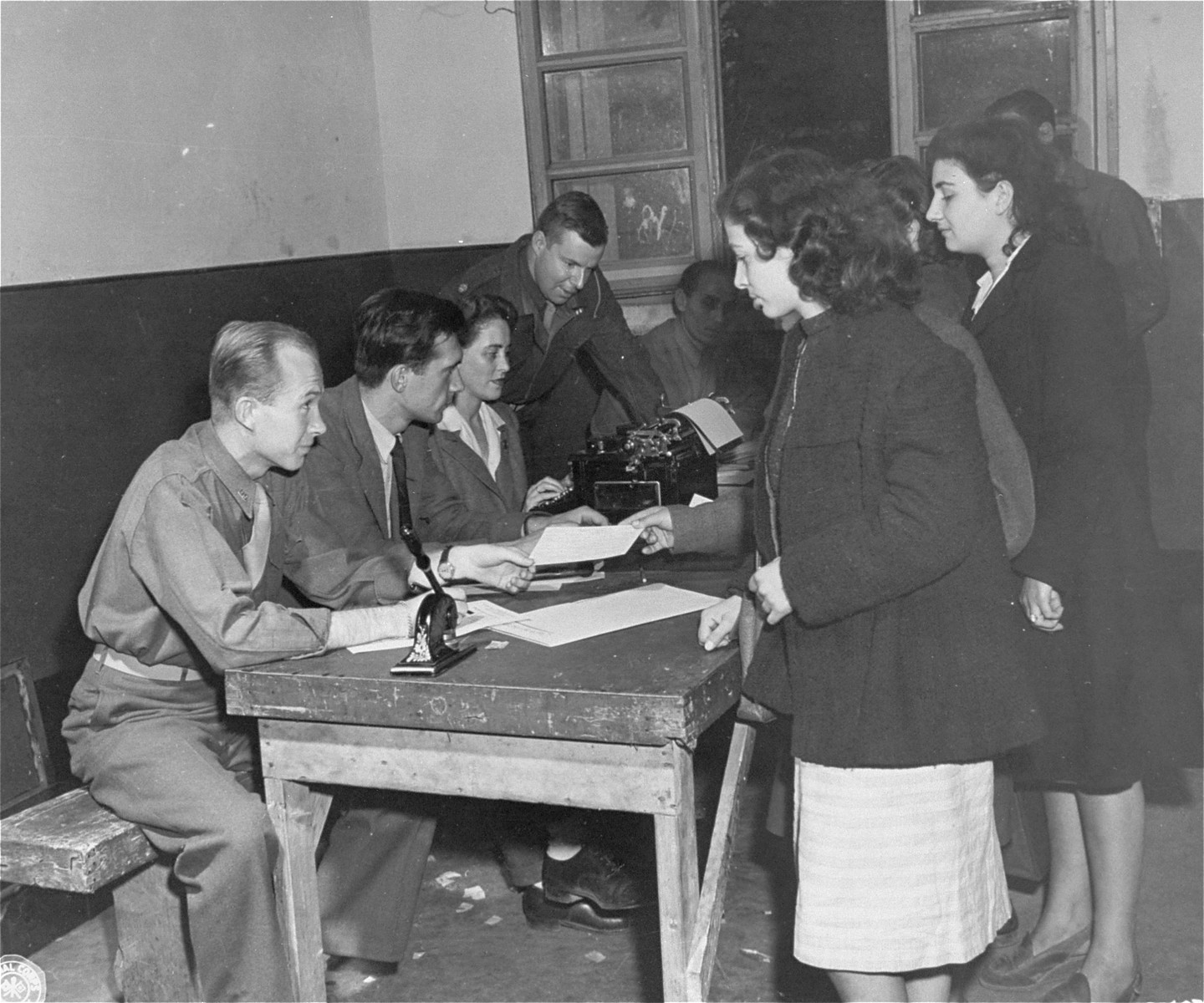 Jewish DPs en route to Palestine undergo a registration process in Rome.  Among those pictured are Eugene Hammond, representative of the Intergovernmental Commission on Refugees, and Major George Hartman, Allied Commission Repatriation Officer.