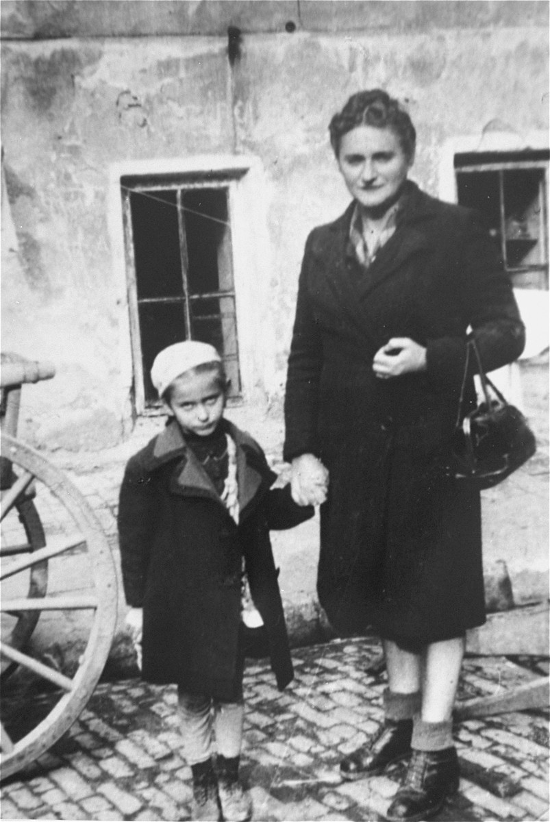 Thea and her mother stand in a couryard in Lublin, Poland shortly after liberation.